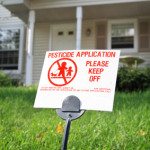 Pesticide warning sign on the lawn in front of a house